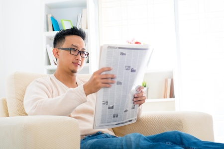 Southeast Asian male reading news paper sitting on sofa at home, indoor lifestyle photo