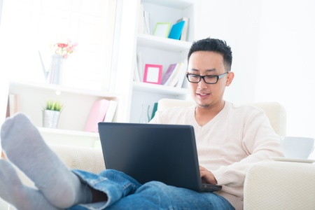 southeast asian: Southeast Asian male using internet at home, sitting on sofa relaxing Stock Photo