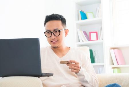 東南亞男性控股信用卡網上購物在家 版權商用圖片