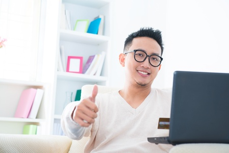 Thumb up Southeast Asian male internet shopping at home photo