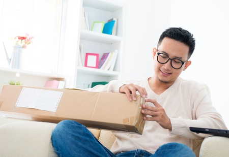 Southeast Asian male received an express parcel and open it at home photo
