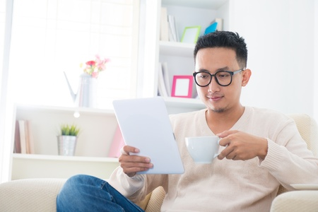 Southeast Asian male drinking coffee  tea and using digital computer tablet at home