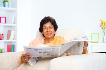read news: Mature 50s Indian woman reading news paper on sofa at home