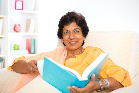 Mature 50s Indian woman reading a book at home photo