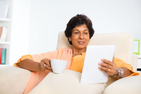 Mature 50s Indian woman drinking coffee  tea and using digital computer tablet at home photo