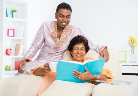 Mature 50s Indian woman reading a book with her son at home photo