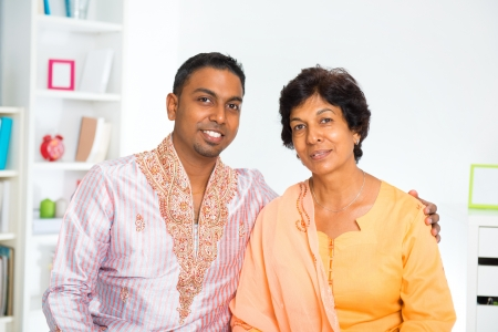 Mature 50s Indian woman and her 30s son sitting at home photo