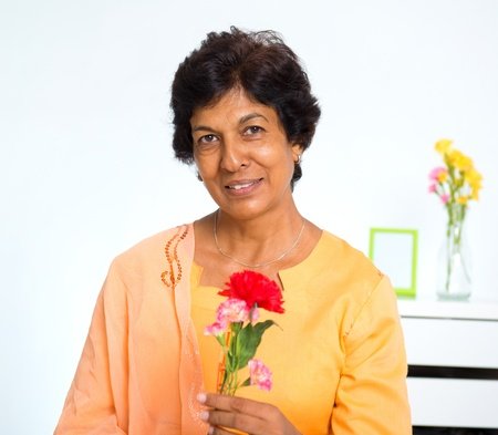 Portrait of a mature Indian woman holding carnation flower at home photo