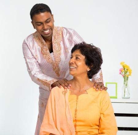 back rub: A lovely mature Indian woman enjoying a shoulder massage from her son at home