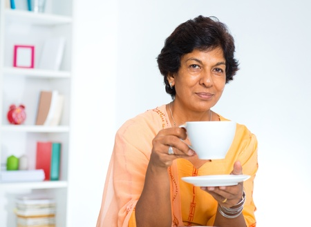 Mature Indian woman drinking coffee  tea at home photo