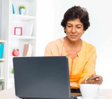 Mature 50s Indian woman holding credit card online shopping at home photo