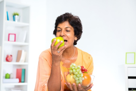 Mature 50s Indian woman eating fruits at home photo