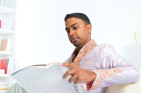 Middle age 30s Indian male reading news paper on sofa at home photo