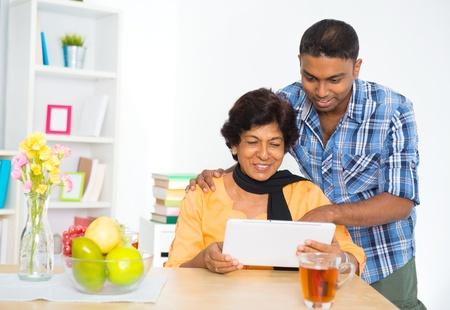 使用數字電腦平板電腦在家裡成熟的50歲印度籍女子和兒子 版權商用圖片