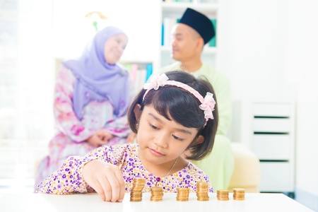 muslim: Southeast Asian girl money savings concept. Asian family living lifestyle. Stock Photo