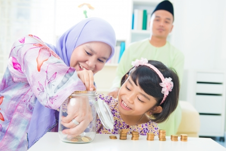 finance girl: Southeast Asian family saving money at home. Muslim family living lifestyle.