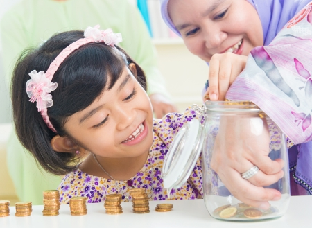 Muslim mother and daughter saving money at home. Southeast Asian family living lifestyle. photo