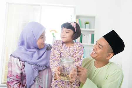 money jar: Southeast Asian family. Muslim girl hand holding money jar at home.