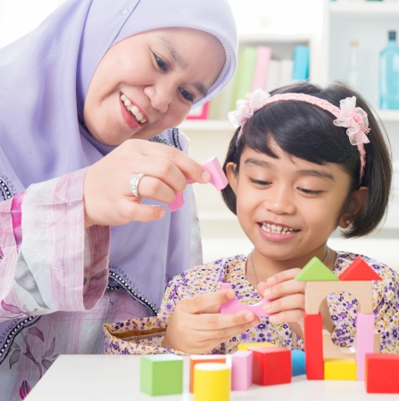 children playing with toys: Muslim family building wooden house toy. Southeast Asian family living lifestyle.