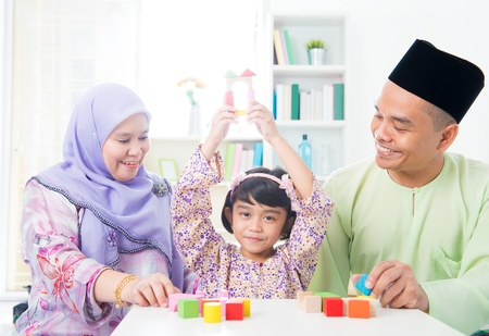 Southeast Asian child achievement. Muslim family playing games. photo