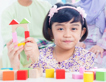 Muslim child building wooden house. Southeast Asian girl playing woodblock house at home. Stock Photo - 16856832
