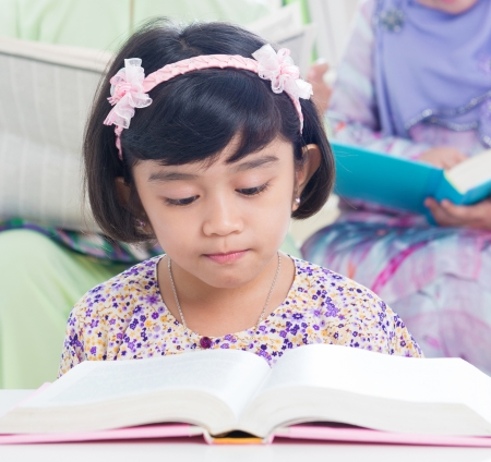 Muslim family living lifestyle. Southeast asian family reading book. photo