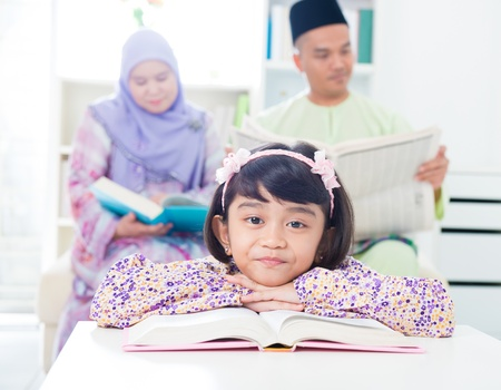 Southeast Asian girl reading at home. Muslim family living lifestyle photo