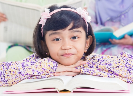 Muslim girl reading book at home. Southeast Asian family living lifestyle photo