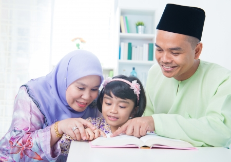 father teaching daughter: Muslim family reading book at home. Southeast Asian family living lifestyle Stock Photo