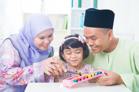 Southeast Asian family playing music instrument. Muslim family living lifestyle. photo