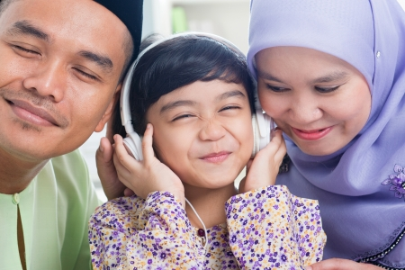 Southeast Asian family listen mp3, sharing headphone. Muslim family living lifestyle Stock Photo - 16856846