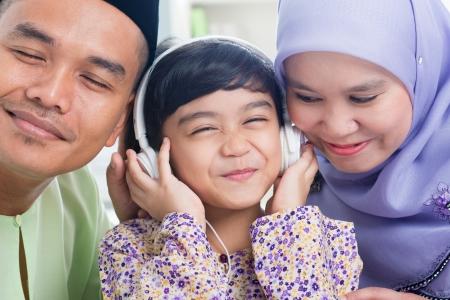 Southeast Asian family listen mp3, sharing headphone. Muslim family living lifestyle Stock Photo - 16856846
