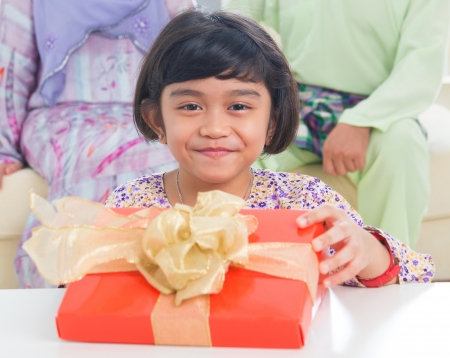 Ssoutheast Asian girl with birthday present. Muslim family living lifestyle. photo