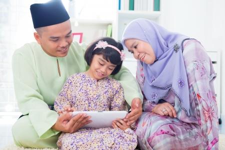 femmes muslim: Du Sud-Est asiatique de la famille en utilisant internet ordinateur � la maison. Mode de vie musulman famille vivant