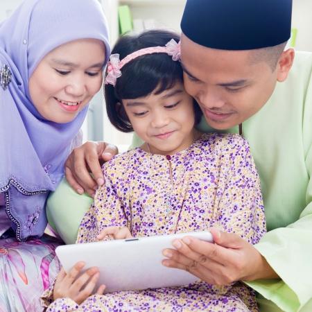 東南亞的家庭在家裡上網衝浪。穆斯林家庭生活的生活方式