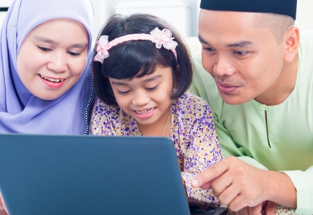Southeast Asian family browsing internet at home. Muslim family living lifestyle Stock Photo - 16856959