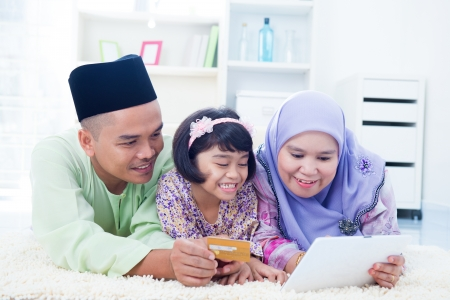 Southeast Asian family online shopping with credit card at home. Muslim family living lifestyle. photo