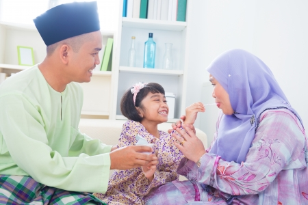 Southeast Asian child feeding mother yogurt. Malay Muslim family living lifestyle photo