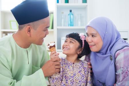 malay food: Southeast Asian girl feeding ice cream to father. Malay Muslim family lifestyle
