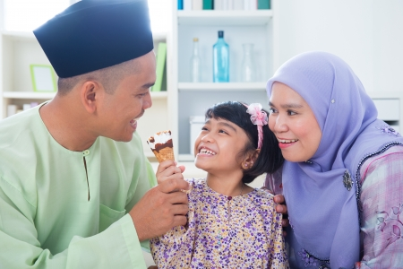 familia comiendo: Sudeste asiático alimentación niña helado al padre. Estilo de vida familia musulmana malaya