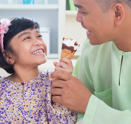 Cute Southeast Asian girl feeding ice cream to father. Malay Muslim family lifestyle photo