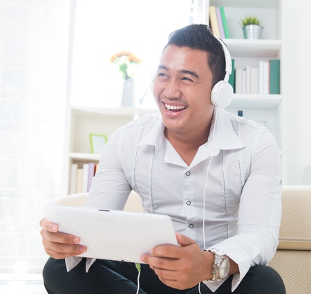 Asian man listen music with headphone, sitting on floor at home. photo