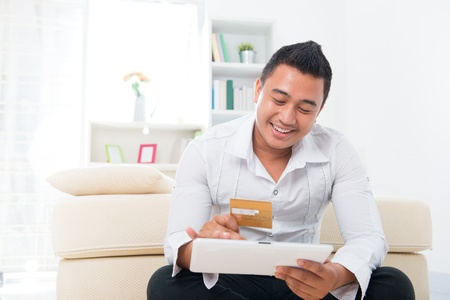 Happy Southeast Asian man online shopping, hands holding credit card and computer tab sitting at home. photo
