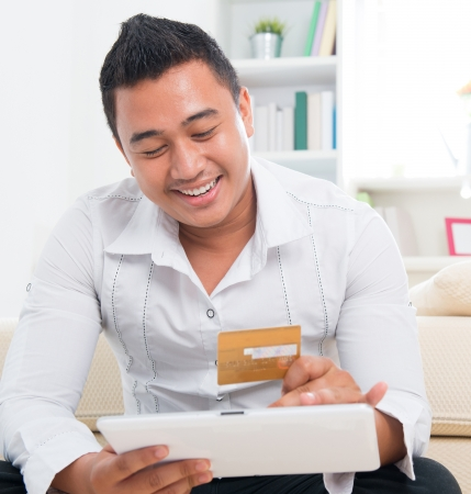 Southeast Asian man online shopping, hands holding credit card and computer tab sitting at home. photo