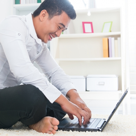logon: Southeast Asian man surfing internet at home, sitting on floor.