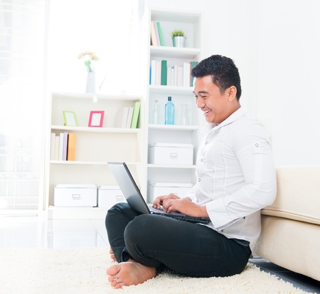 ebusiness: Asian man browsing internet at home, sitting on floor.