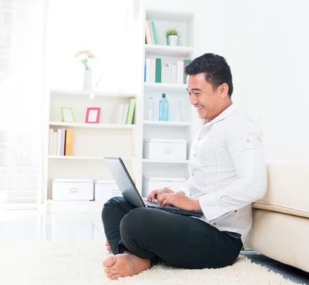 logon: Asian man browsing internet at home, sitting on floor.
