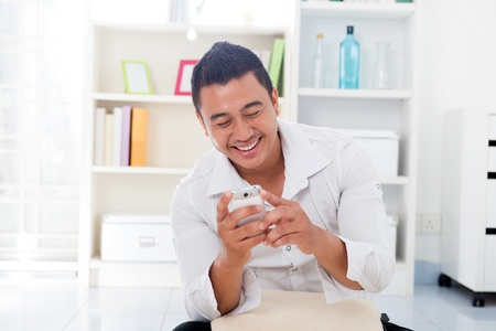 Cheerful Asian male using smartphone at home, looking on screen. photo