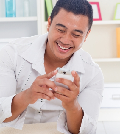 Cheerful Asian man using smartphone at home, looking on screen. photo