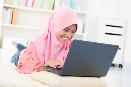 young asian girl: Southeast Asian teenager surfing internet. Muslim teen using notebook at home Stock Photo